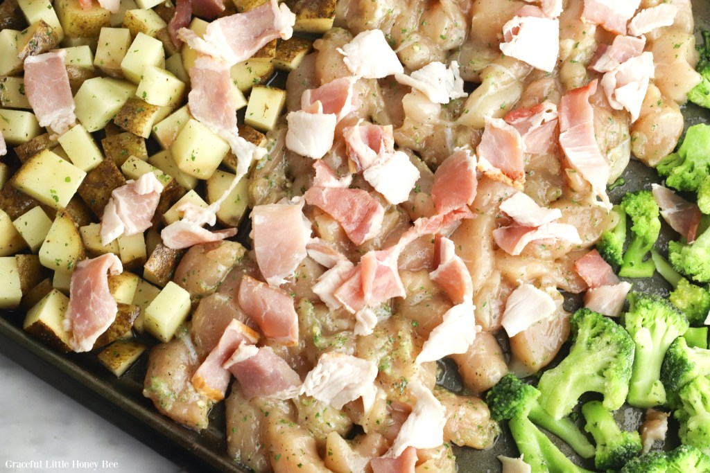 Potatoes, raw chicken, raw bacon and broccoli on a sheet pan before baking.