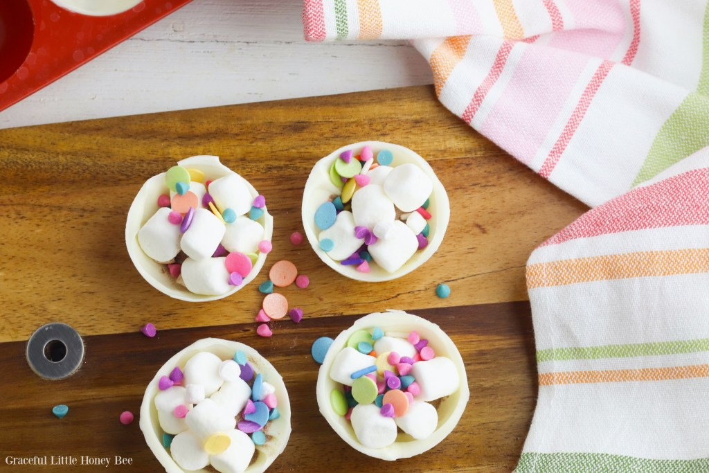 Four half shells of a hot chocolate bomb filled with instant hot chocolate, mini marshmallows and rainbow sprinkles sitting on a wooden cutting board.