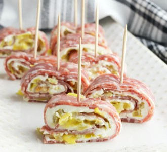 Salami Roll-Ups sitting on a white plate with a toothpick in each one.