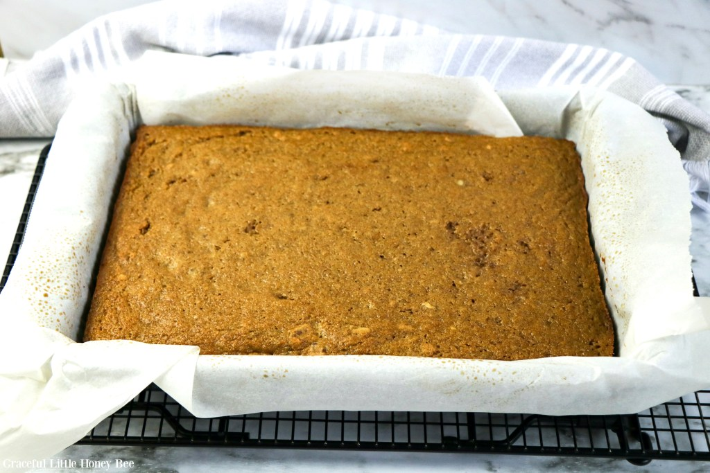 Baked cake sitting in cake pan with parchment paper.