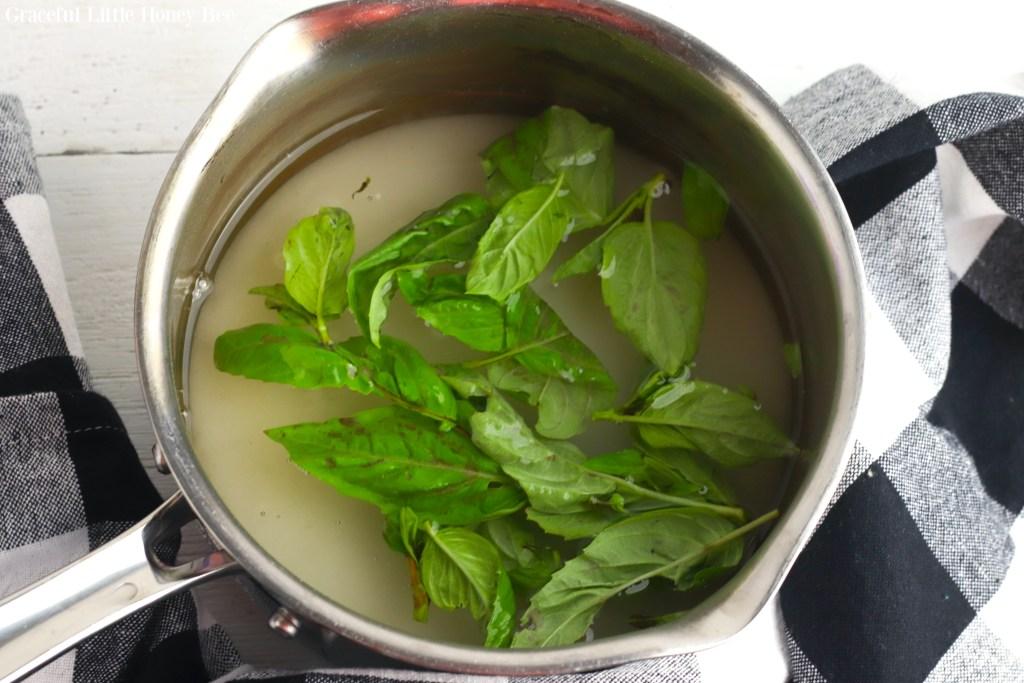 Sugar, water and basil in a saucepan.