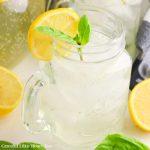 A mason jar full of Basil Sparkling Lemonade garnished with basil and a lemon slice.