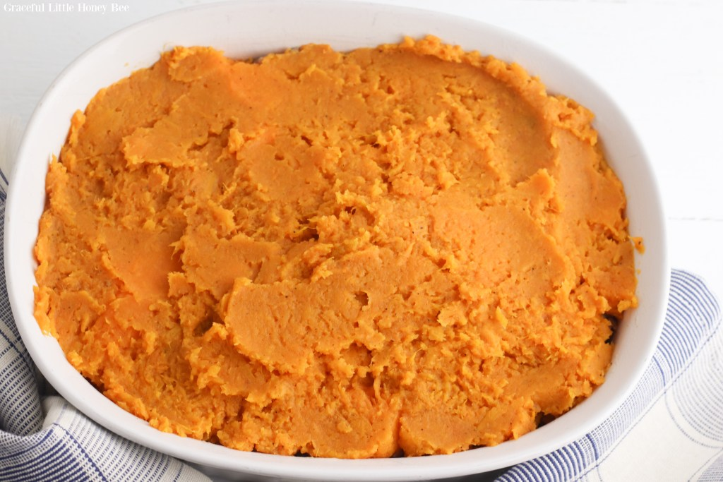 Mashed sweet potato on top of vegetable mixture in white baking dish.