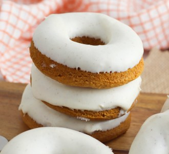 Stack of three donuts sitting on a wooden cutting board.