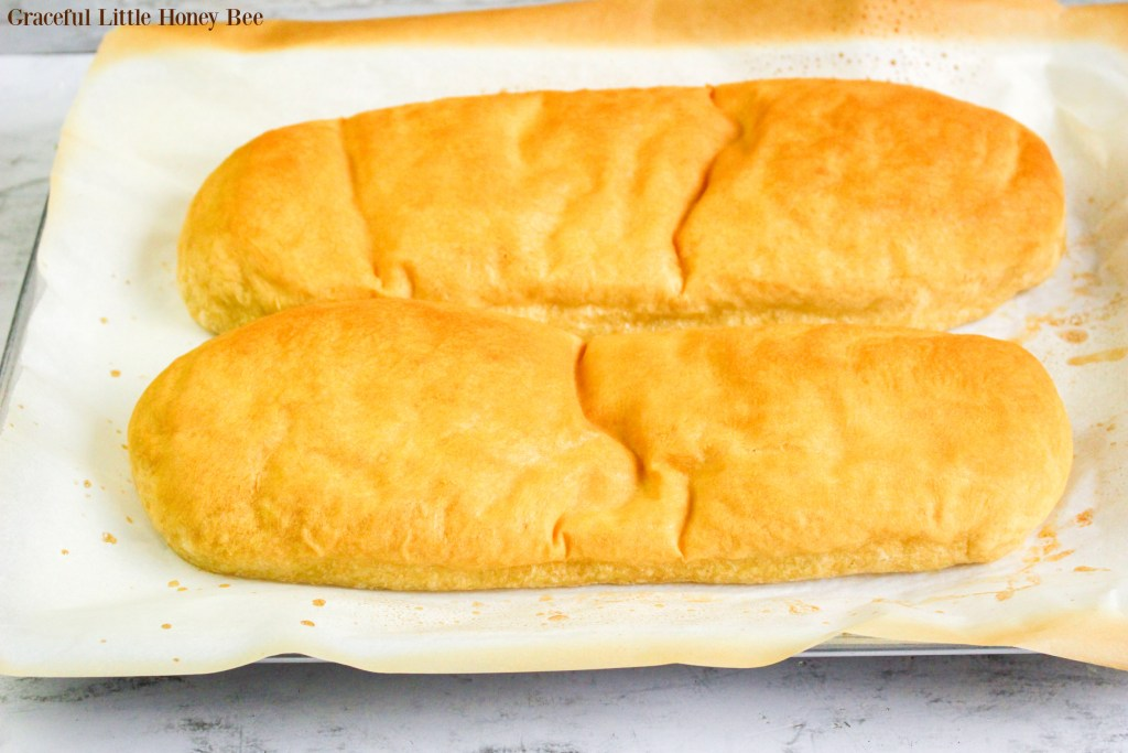 Two loaves of french bread sitting on a baking sheet.