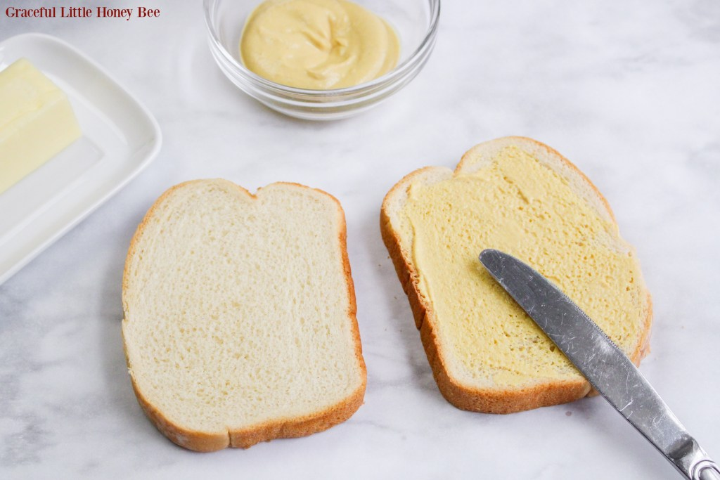 Dijon Mustard being spread on top of sandwich bread.