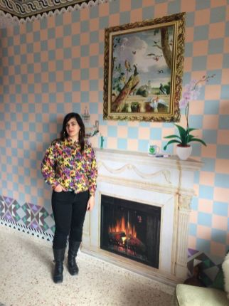 """Banksy Walled off Hotel, Bethlehem, Artist Dominique Pétrin stands by the """"shit happens"""" fireplace."""