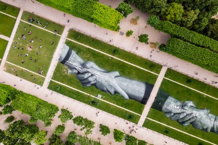 "A giant biodegradable landart painting by French-Swiss artist Saype is pictured Monday June 10, 2019 on the Champ de Mars in front of the iconic Eiffel Tower in Paris, France. With an overall area of 15'000 square meters, the 600 meters long and 25 meters wide painting (likely one of the largest of its kind) was created using biodegradable pigments made out of charcoal, chalk, water and milk proteins. This art piece launches the worldwide project ""Beyond Walls"" aiming at creating the longest symbolic human chain around the world promoting values such as togetherness, kindness and openness to the world. (VFLPIX.COM /Valentin Flauraud)"