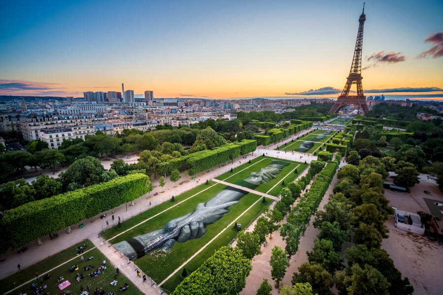 """A giant biodegradable landart painting by French-Swiss artist Saype is pictured on Monday June 10, 2019 on the Champ de Mars in front of the iconic Eiffel Tower in Paris, France. With an overall area of 15'000 square meters, the 600 meters long and 25 meters wide painting (likely one of the largest of its kind) was created using biodegradable pigments made out of charcoal, chalk, water and milk proteins. This art piece launches the worldwide project """"Beyond Walls"""" aiming at creating the longest symbolic human chain around the world promoting values such as togetherness, kindness and openness to the world. (VFLPIX.COM /Valentin Flauraud)"""