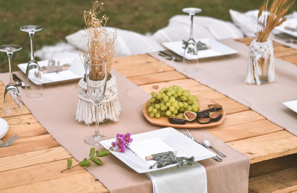 Gedekte tafel met taupe kleurige tafelloper vierkante borden en gedroogde bloemen op houten tafel
