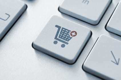 Button with shopping cart icon on a modern computer keyboard.