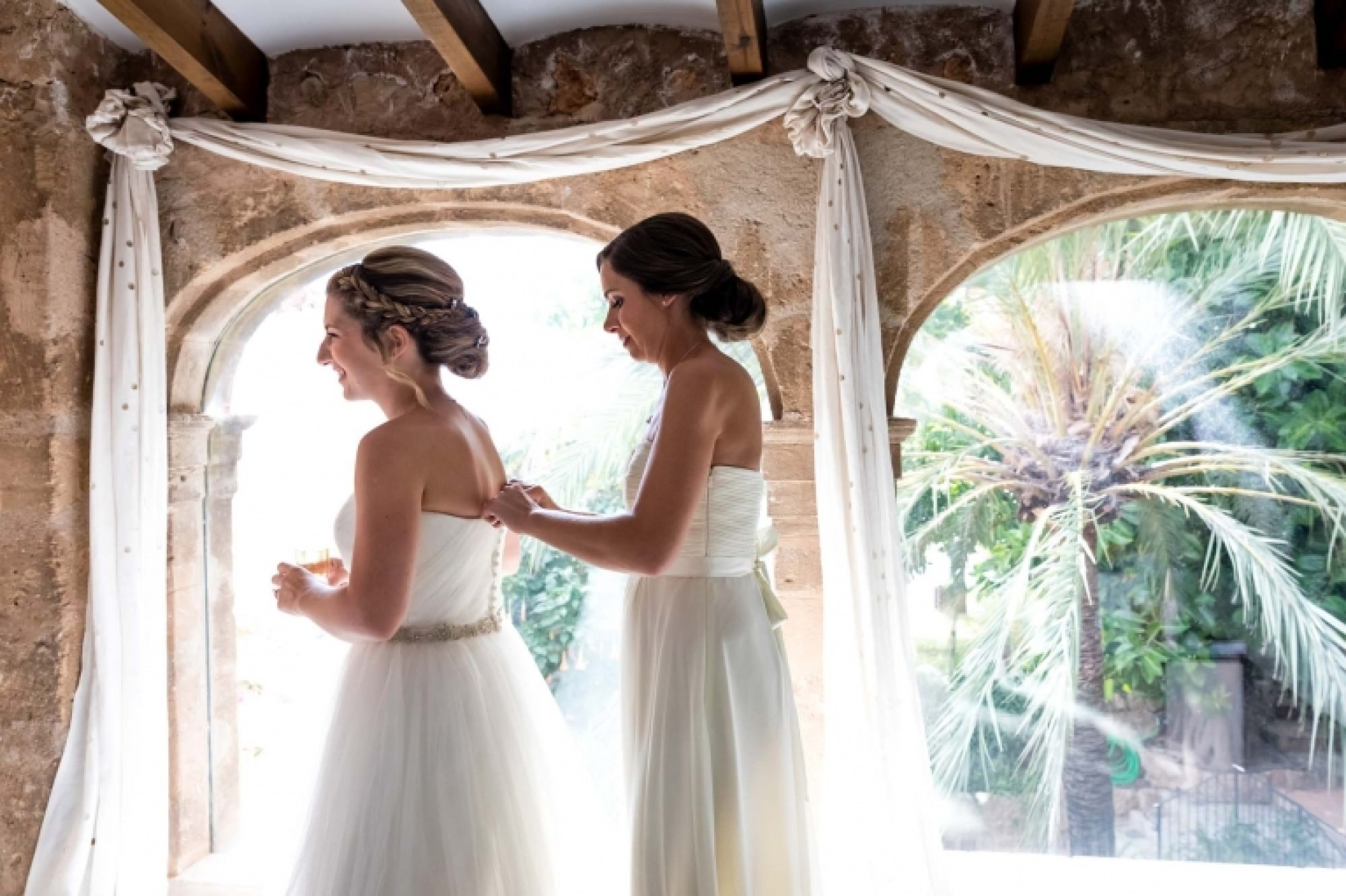 A bridesmaid helps the bride to put on her wedding dress at Hotel Can Vedera in Fornalutx