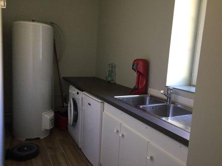 La buanderie de la Maison de Célestin avec grand ballon d'eau chaude, lave-linge, congélateur et évier double-bac