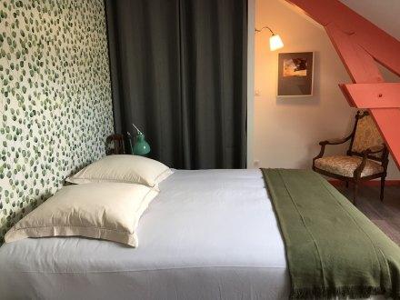 La chambre Magnolia de la Maison de Célestin. Un lit Queen size, une grande penderie fermée d'une rideau, un coin lecture avec fauteuil et liseuse et poutres en bois peint.