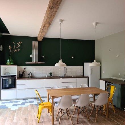 La Maison de Célestin vue de la cuisine aménagée avec grand réfrigérateur, hotte inoxydable et dame-jeanne.