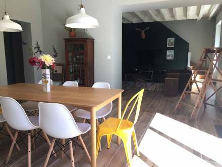 La Maison de Célestin, table de cuisine en bois avec chaises scandinaves et Tollix vue depuis la baie vitrée