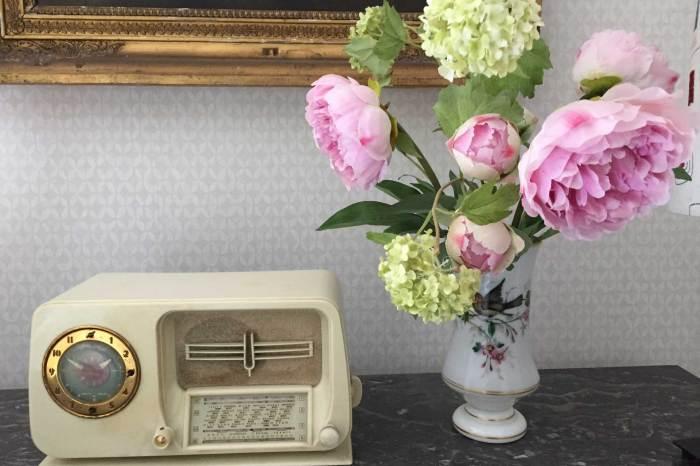 La chambre Oncle Roger de Grand Bouy, détail de décoration, un bouquet de pivoines et viorne dans un vase en opaline peint à côté d'une radio vintage