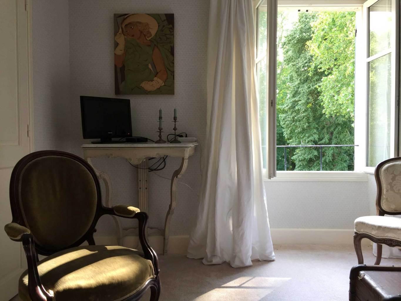 Chambre Oncle Roger de Grand Bouy, la TV écran plat est posée sur une console en bois sculpté, la fenêtre est ouverte.