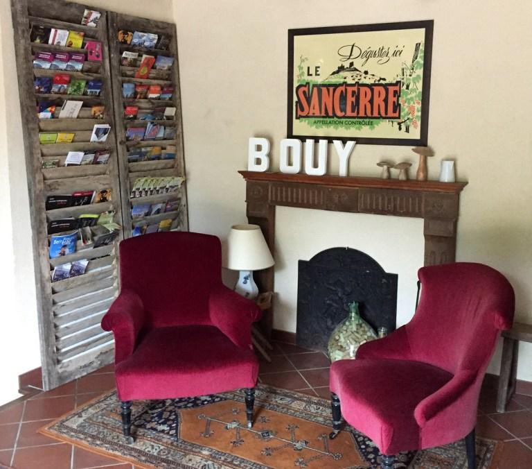 Un coin salon avec 2 fauteuils carpeaux en velours rouge, dans d'anciennes persiennes en bois sont rangées des brochures touristiques, au mur, au dessus d'une cheminée est accrochée une affiche vintage de Sancerre