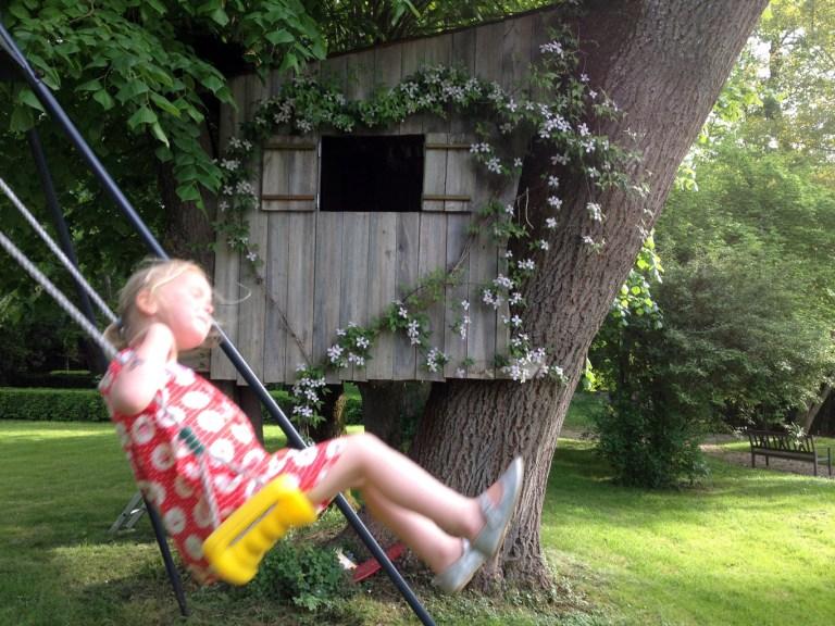 Dans le parc de Grand Bouy, une fillette fait de la balançoire devant une cabane dans les arbres ornée d'une clématite Montana taillée en coeur