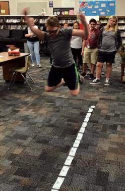 A student leaps along a line of dollar bills