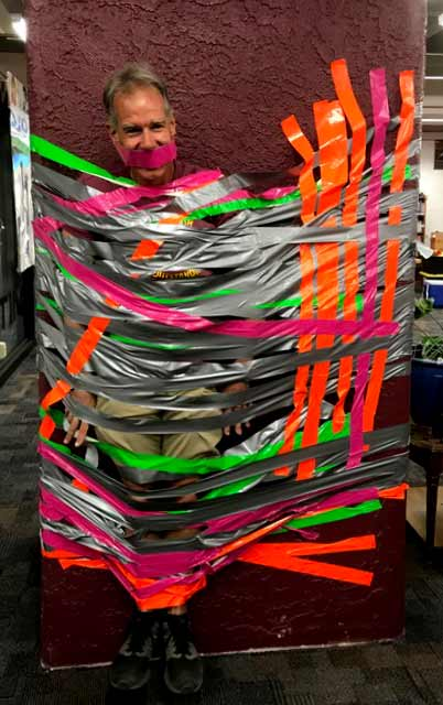 A teacher is tied to a pillar with multiple colors of duct tape.