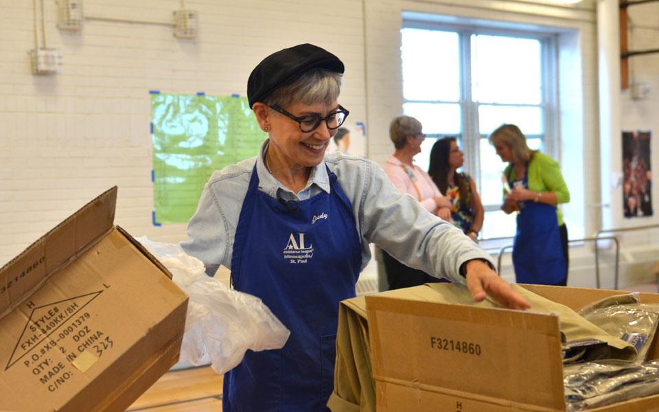 Assistance League volunteer sorting school uniforms for Clothes For Kids Program