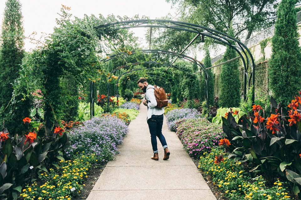 young hipster walking through public urban garden