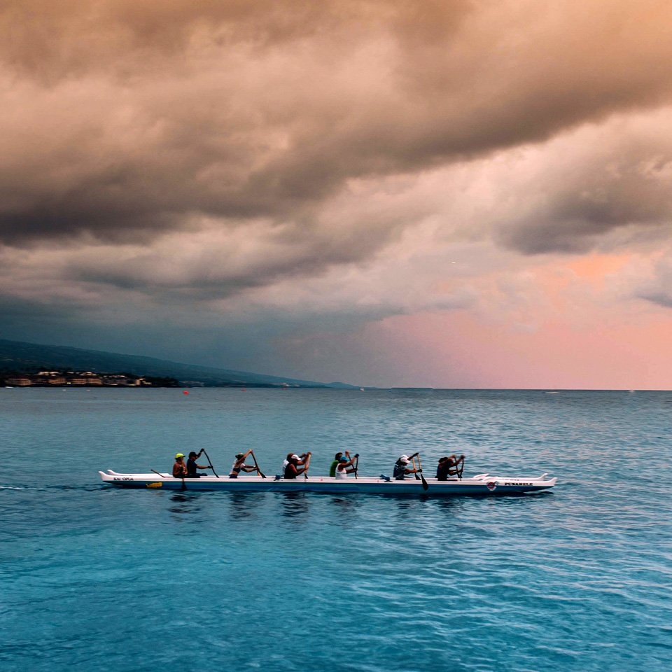 rowing teams out on open water under pink cloudy skies
