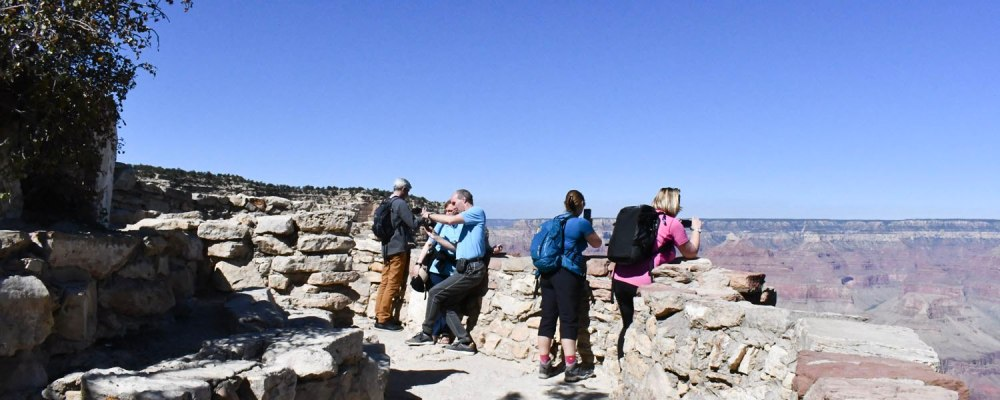 Vegas to Grand Canyon tourists look out into the canyon and enjoy the beautiful view.