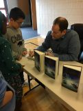 Author Brandon Mull signing books for students