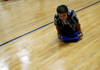 Photo of student riding on floor roller