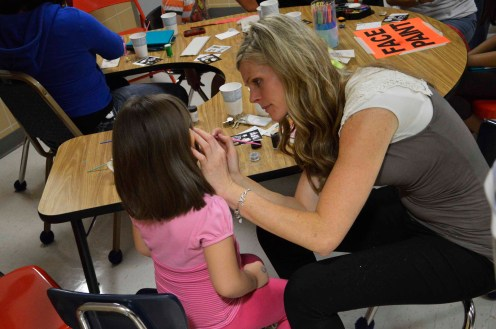 Photo of teacher painting student's face