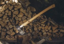 axe on top of log by wood pile