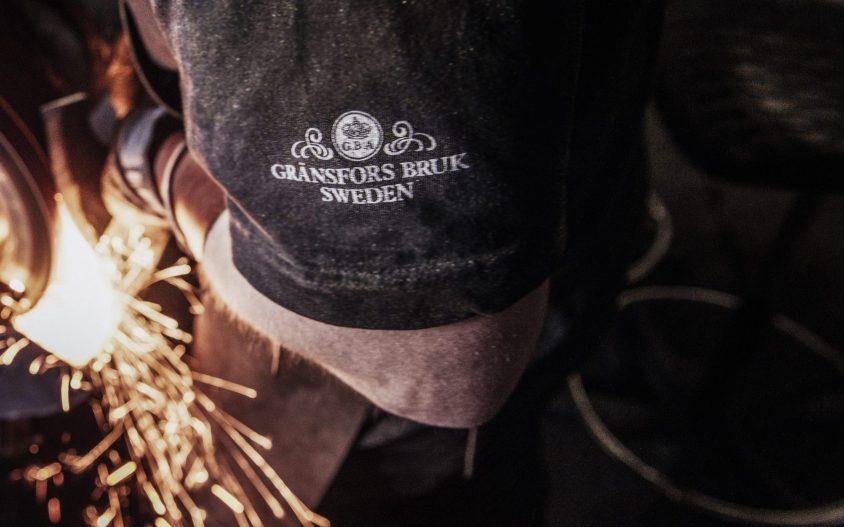 Blacksmith wearing Gransfors Bruk Sweden shirt with white logo on sleeve.