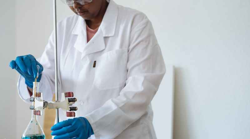 focused african american researcher conducting biochemical experiment in clinic