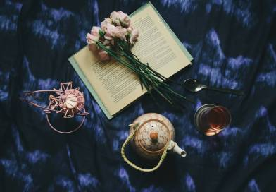 opened book with flowers placed on silk near teapot