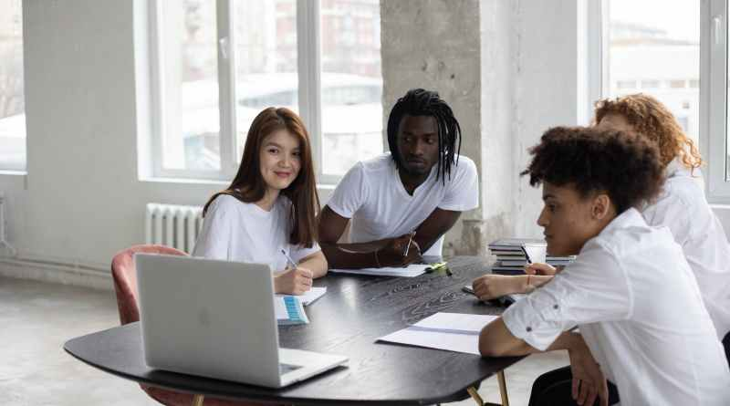 multiethnic students gathering around table with laptop