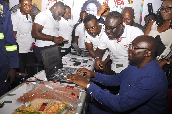 Vice-President Dr Mahamudu Bawumia (seated) being assisted by Mr Agya Yaw, Research and Planning Unit, YEA, to launch the YEA Job Centre Programme