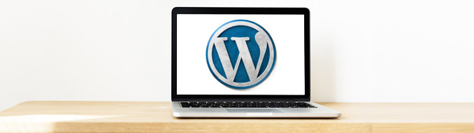 Laptop sitting on a wooden table with the WordPress logo on the screen