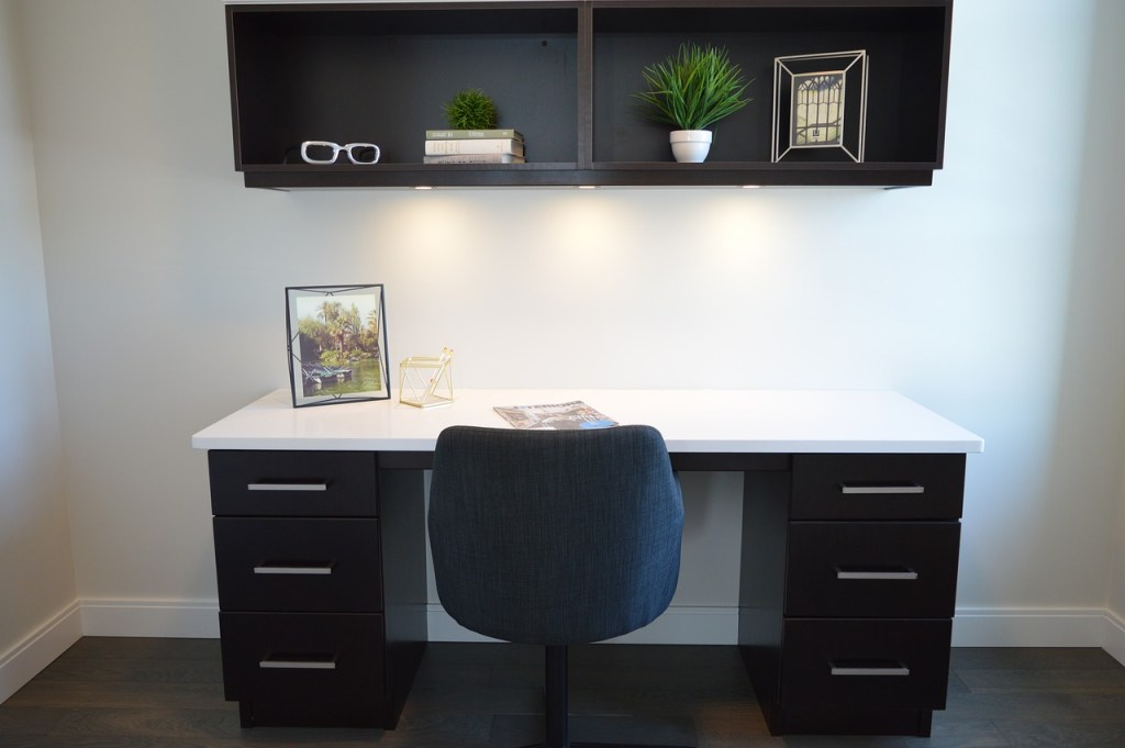 modern minimalist home office with comfy simple chair and eye glass also bookshelf