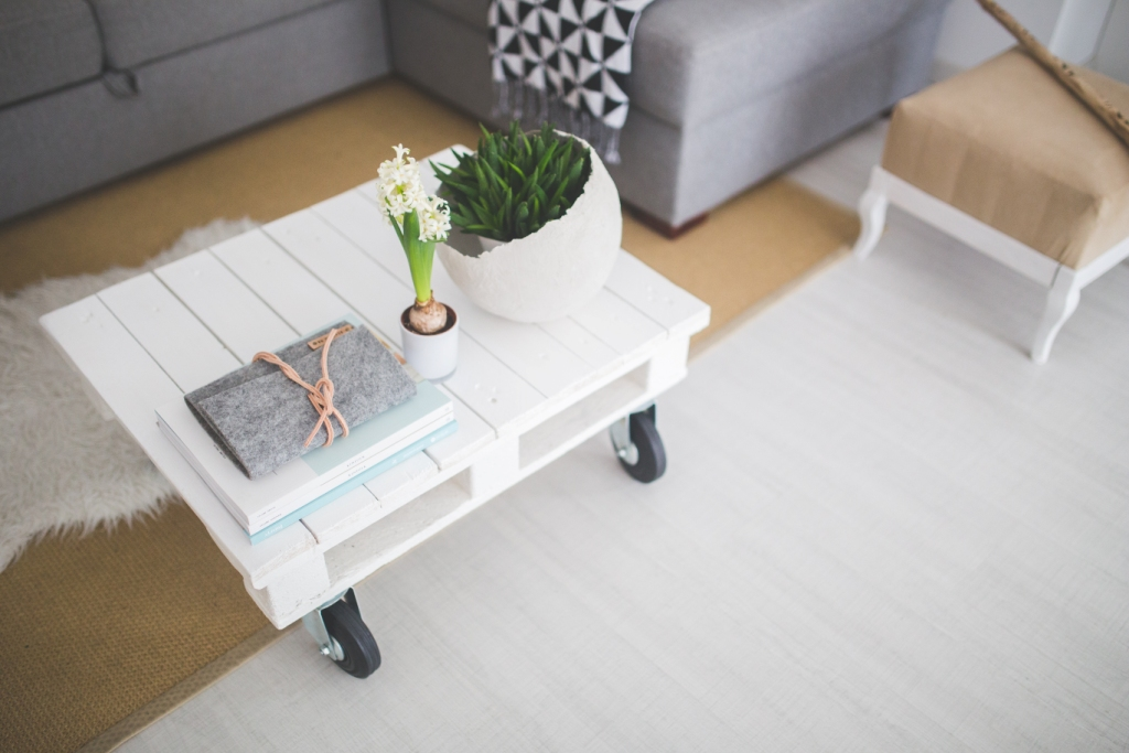awesome white pallet as coffee table with wheels and grey sofa also floral decor