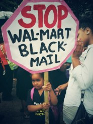 child_holds_stop_walmart_black_mail_sign