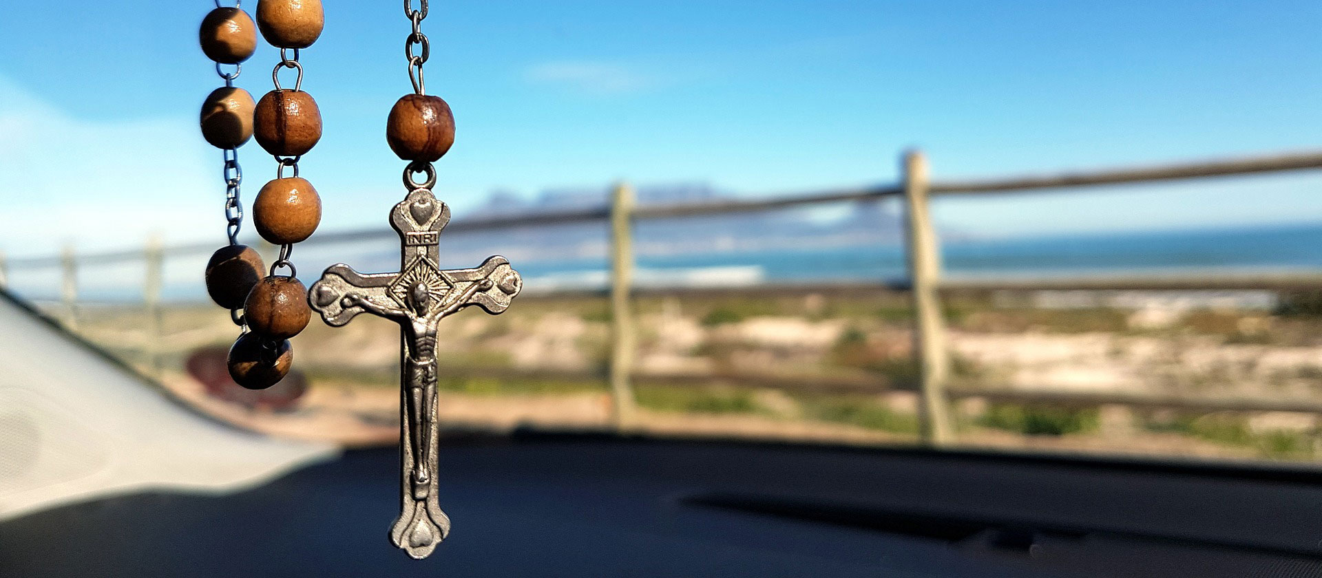 Rosary hanging in car with ocean view in background