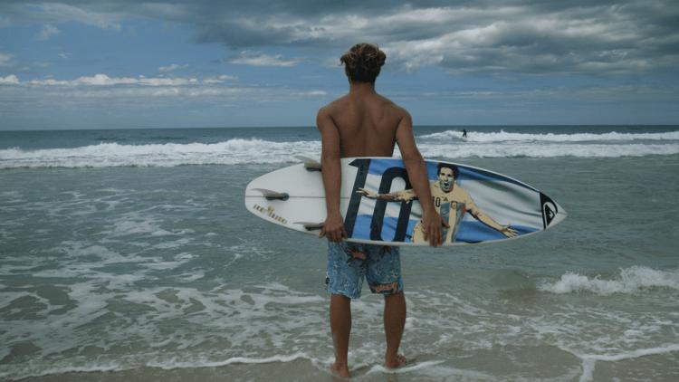 Hermosa postal de Muñiz, la tabla y una de las playas cariocas que elige para entrenarse.