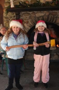 yule log celebration two girls holding axe