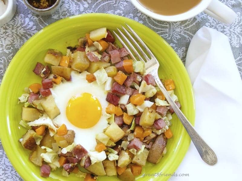 Overhead shot of corned beef hash with a sunny side up egg in the center. On a lime green plate with a silver fork.