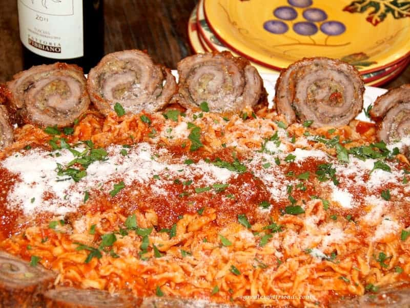 Beef Braciole served with pasta and red sauce.