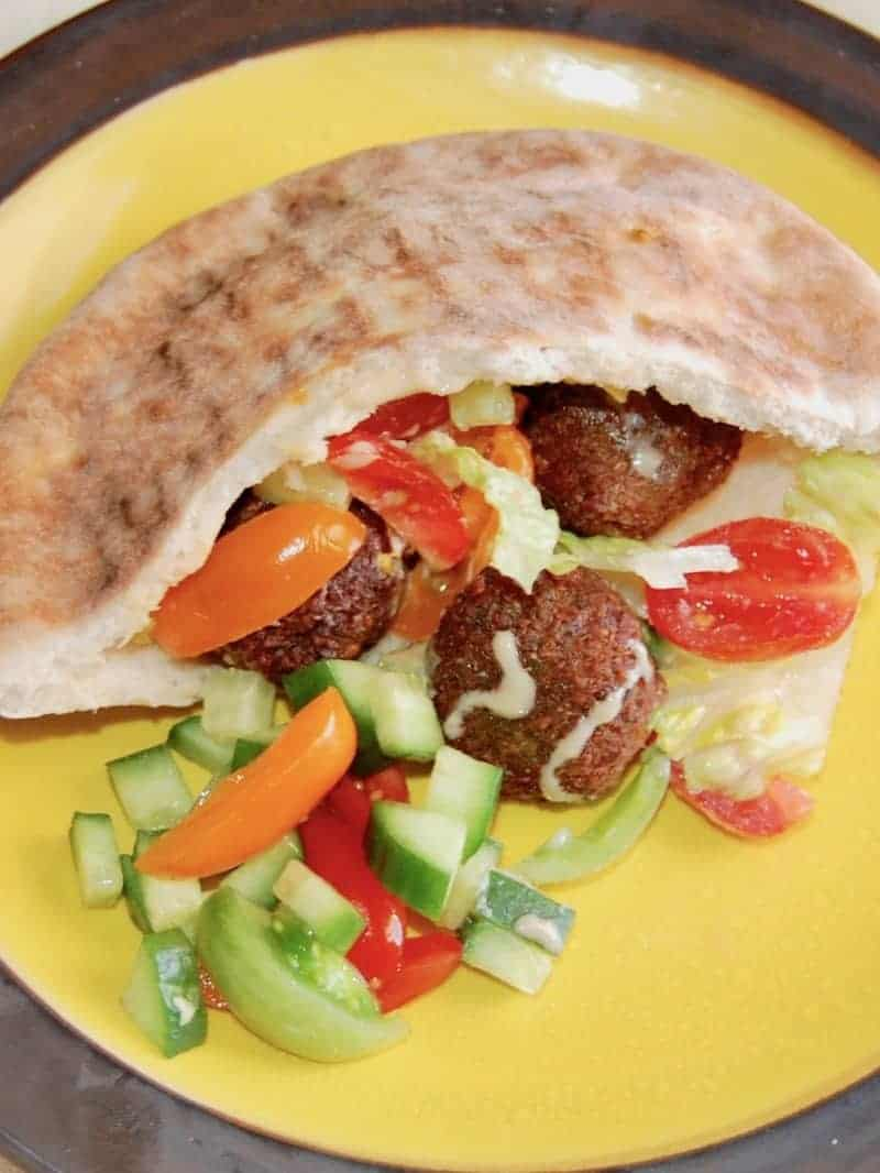 A Falafel served in a pita on a yellow plate with chop fresh vegetables.