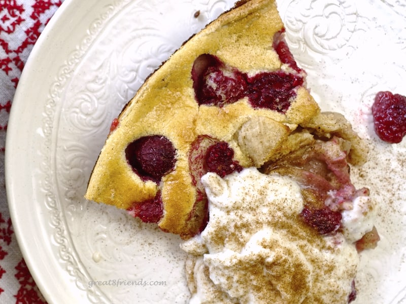 Overhead shot of one slice of Dutch Baby with ricotta cream and cinnamon sprinkled on top.
